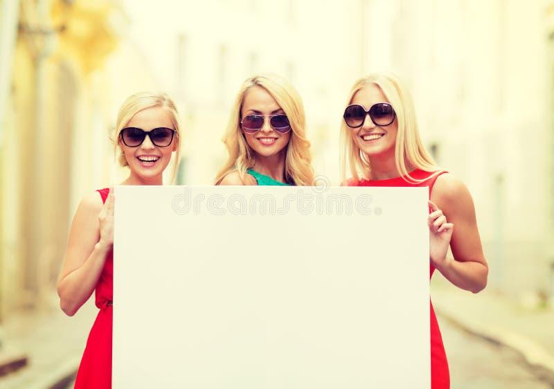 Tre donne bionde felici con il bordo bianco in bianco fotografie stock