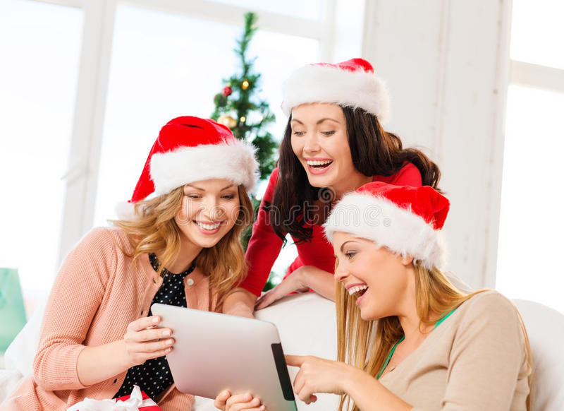 Tre donne in cappelli dell'assistente di Santa con il pc della compressa fotografia stock