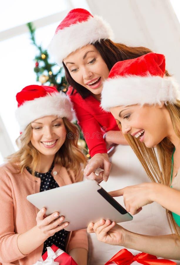 Tre donne in cappelli dell'assistente di Santa con il pc della compressa immagini stock