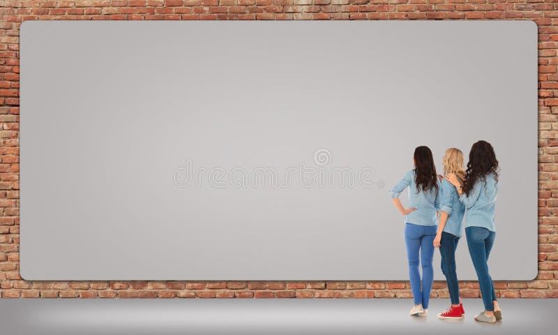 Tre donne che esaminano un grande tabellone per le affissioni in bianco immagini stock