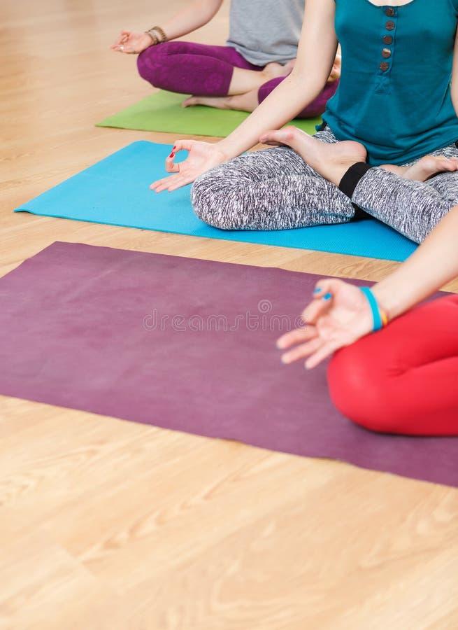 Tre donne che fanno yoga, sedendosi nella posizione di Lotus e nel meditare immagine stock