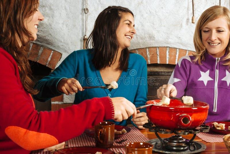 Tre donne che hanno cena della fonduta fotografia stock
