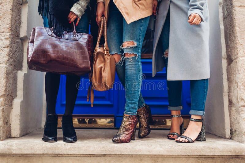 Tre donne che indossano le scarpe e gli accessori alla moda all'aperto Concetto di modo di autunno Signore che tengono le borse f immagine stock libera da diritti