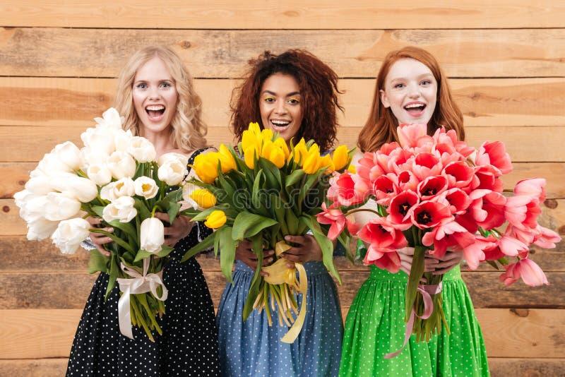Tre donne che mostrano i mazzi dei fiori alla macchina fotografica fotografie stock libere da diritti