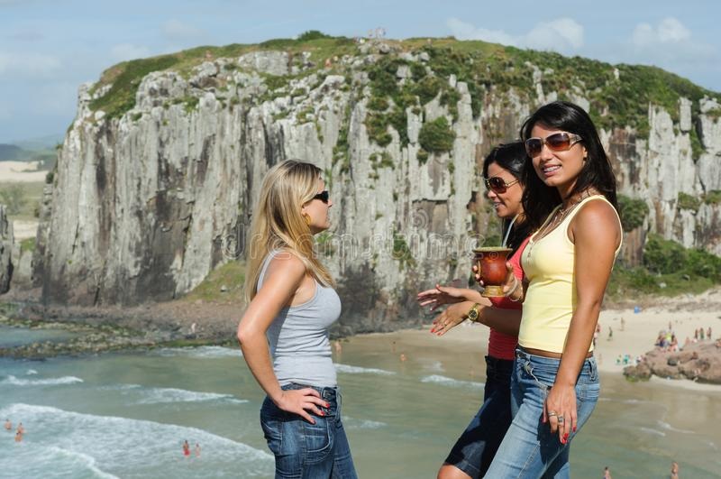 Tre donne che prendono chimarrão sulla spiaggia di Torres fotografia stock libera da diritti