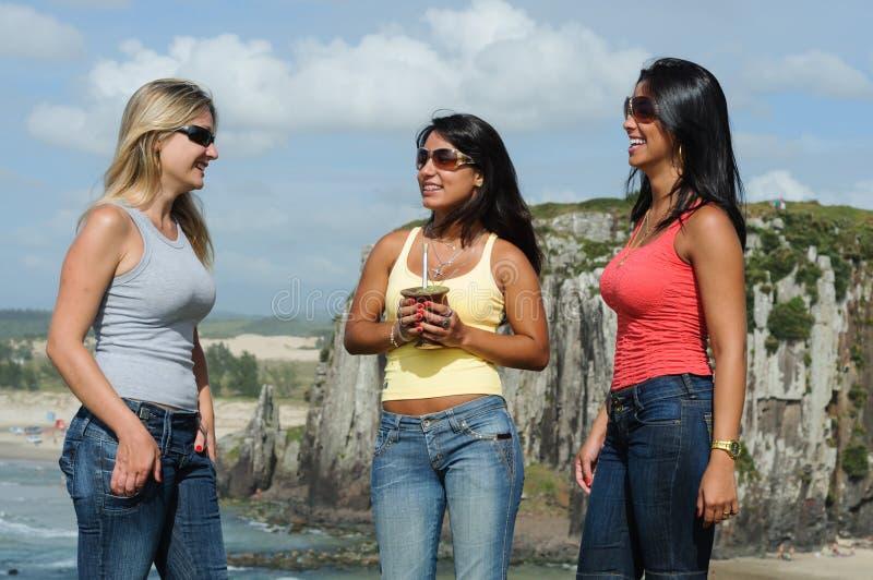 Tre donne che prendono chimarrão sulla spiaggia di Torres fotografie stock