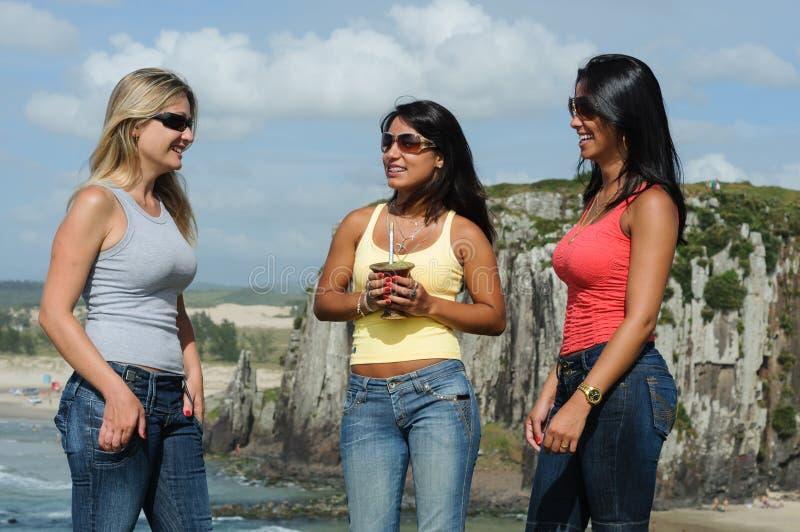 Tre donne che prendono chimarrão sulla spiaggia di Torres immagini stock libere da diritti