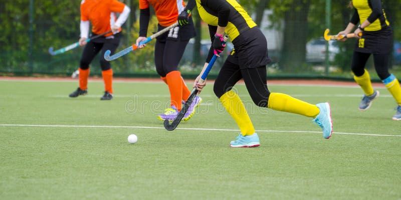 Tre donne combattono per controllo della palla durante il gioco di hockey su prato fotografia stock libera da diritti