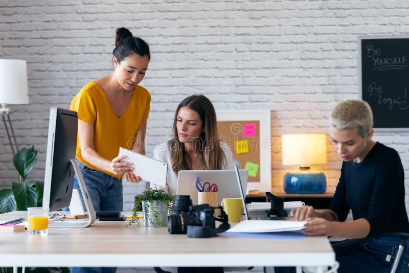 Tre donne d'affari moderne parlano e rivedono i lavori più recenti fatti sul tablet digitale in un'area di lavoro comune fotografia stock libera da diritti