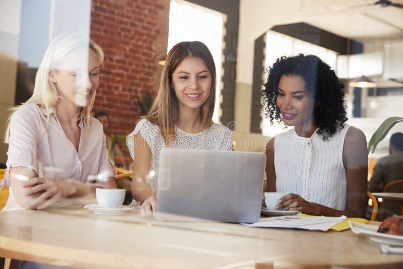 Tre donne di affari si incontrano in caffetteria sparata attraverso la finestra fotografie stock libere da diritti