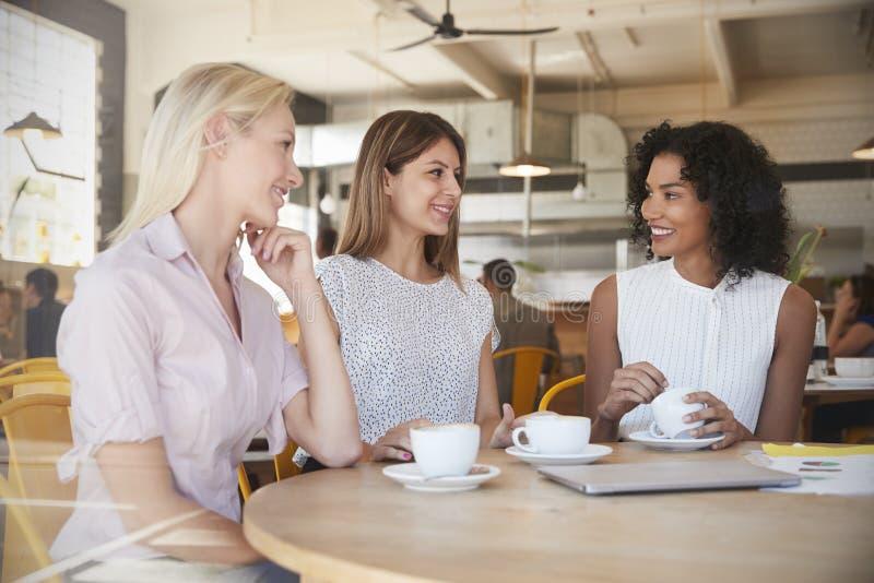 Tre donne di affari si incontrano in caffetteria sparata attraverso la finestra fotografia stock libera da diritti