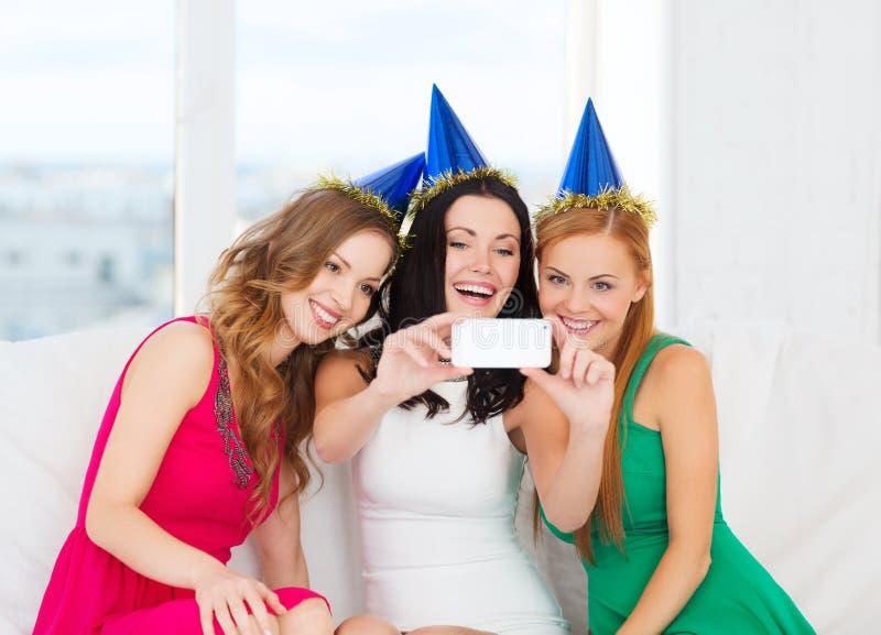 Tre donne sorridenti in cappelli divertendosi con la macchina fotografica fotografia stock