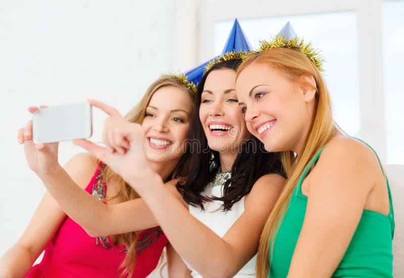 Tre donne sorridenti in cappelli divertendosi con la macchina fotografica immagini stock libere da diritti