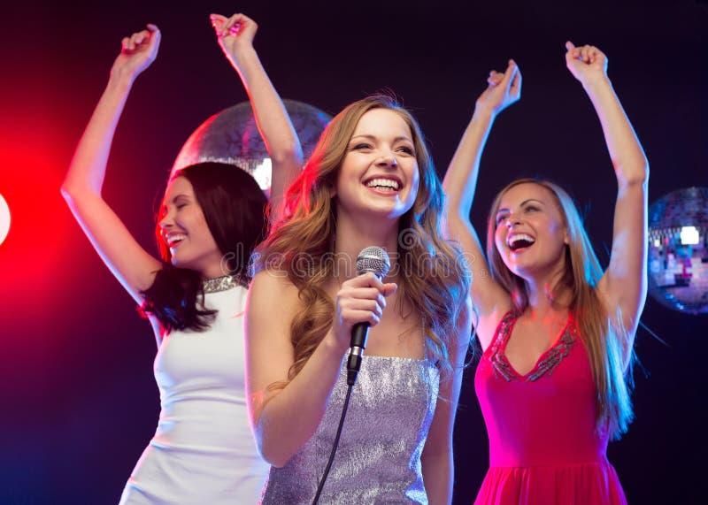 Tre donne sorridenti che ballano e che cantano karaoke immagine stock libera da diritti