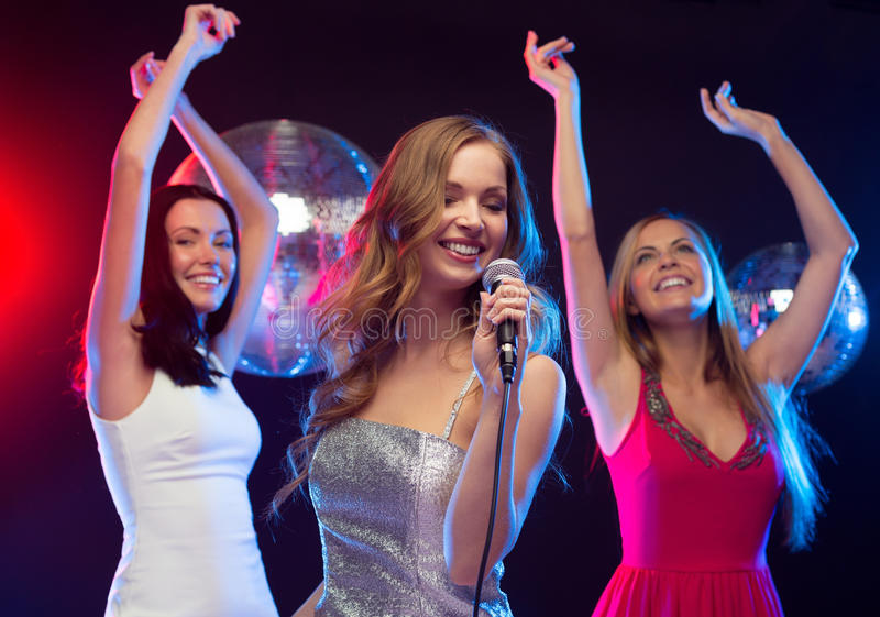Tre donne sorridenti che ballano e che cantano karaoke immagini stock libere da diritti