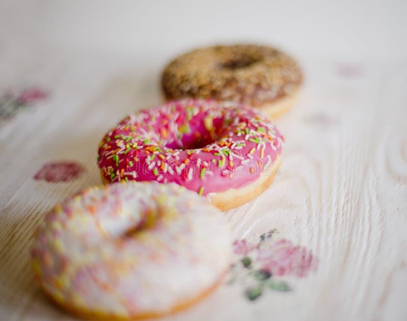 Tre donuts på en bakgrund i stilen av en sjaskig stil fotografering för bildbyråer