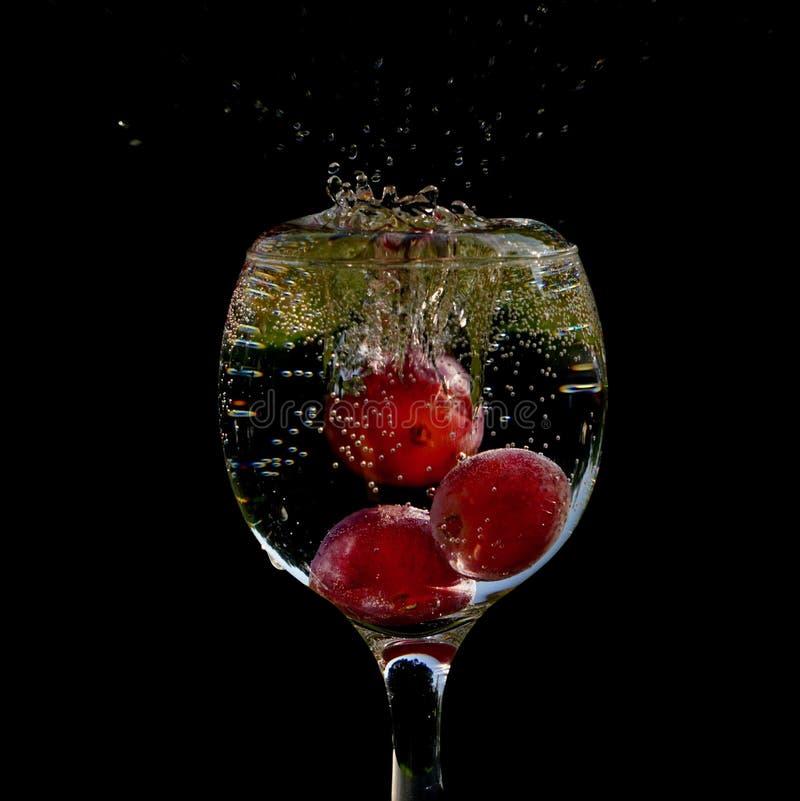 Tre druvor som faller in i ett exponeringsglas av vatten royaltyfria bilder
