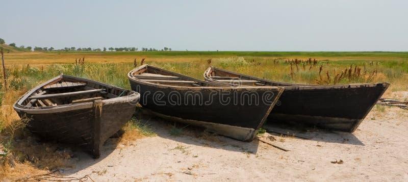 Tre ensamma fiskebåtar på ett sandigt shorelinelandskap arkivfoton