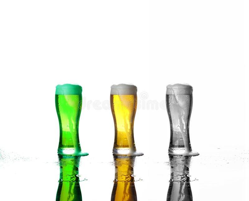Tre exponeringsglas av öl: grönt öl, öllager, en svartvit bild av öl med skum på en vit bakgrund arkivfoton