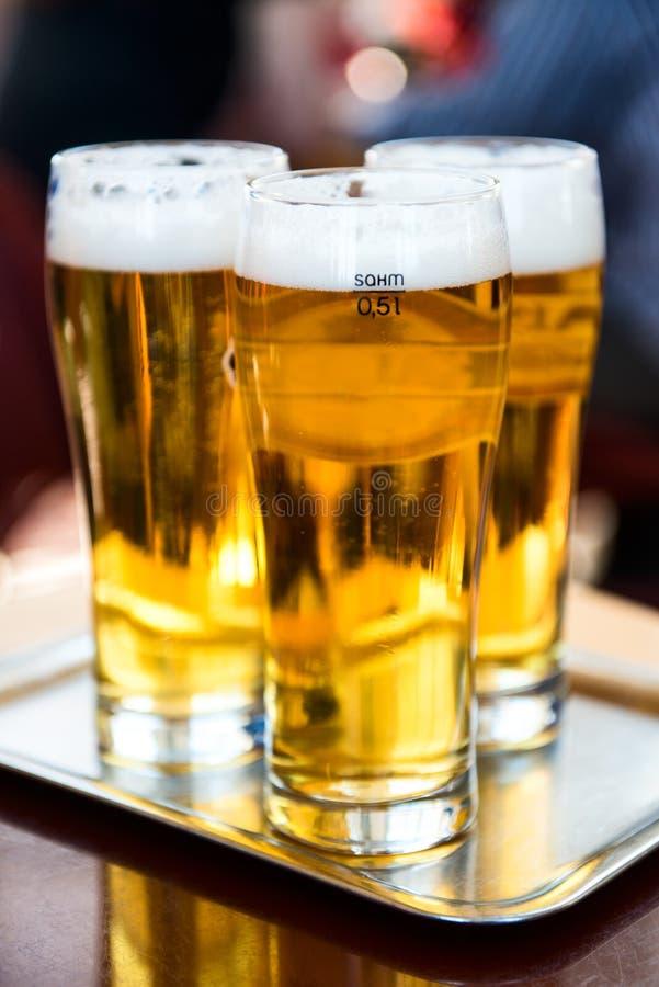 Tre exponeringsglas av öl på silvermagasinet royaltyfri fotografi