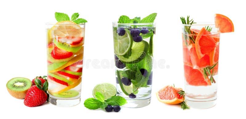 Tre exponeringsglas av frukt ingett vatten som isoleras på vit arkivbilder
