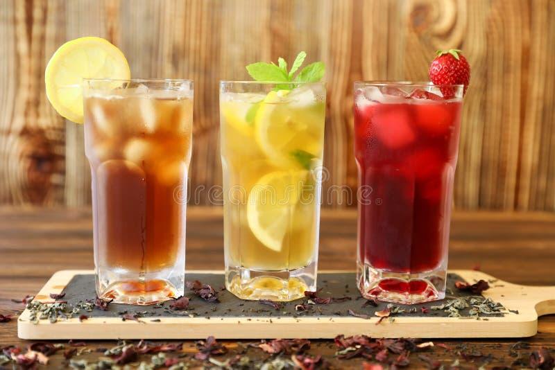 Tre exponeringsglas av olika kalla tedrinkar svärtar, gräsplan med citronen och mintkaramellen, hibiskusteer arkivbilder