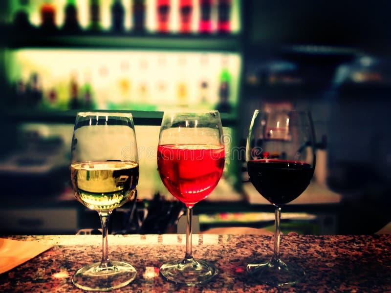 Tre exponeringsglas av olika sorter av vin på stången - vinbegrepp fotografering för bildbyråer