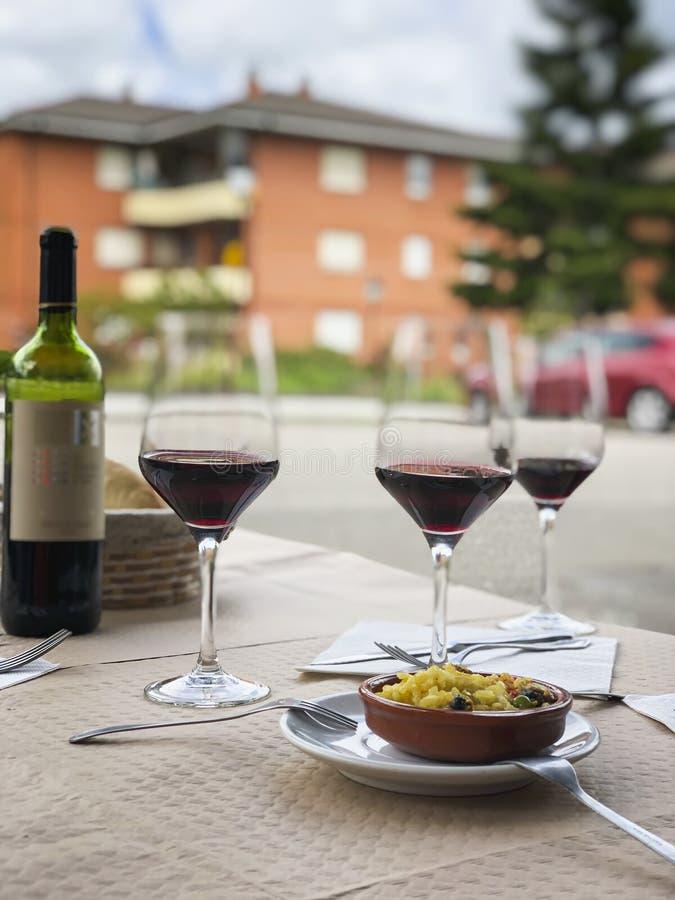 Tre exponeringsglas av rött vin, flaskan av vin och kocks komplimang, liten platta av paella som tjänas som på utomhus- terrass f arkivbild