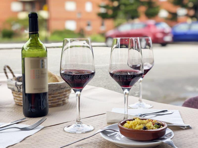 Tre exponeringsglas av rött vin, flaskan av vin och kocks komplimang, liten platta av paella som tjänas som på utomhus- terrass f arkivfoton