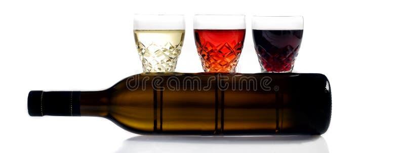 Tre exponeringsglas av vin, exponeringsglas, vitt vin, rött vin, rosa vin, vit bakgrund, flaska av vin arkivbilder