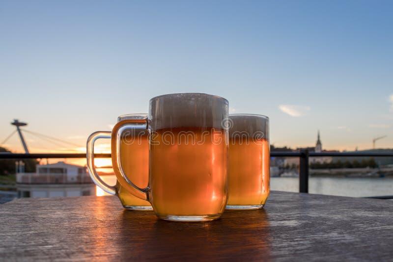 Tre exponeringsglas för ljust öl på trätabellen på bakgrundshimmel och solnedgång arkivfoto