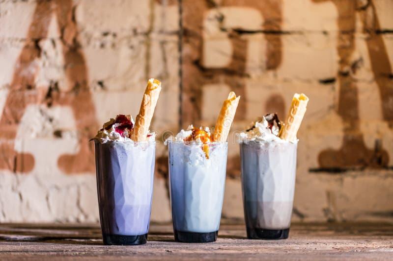 Tre exponeringsglas med en läcker milkshake med rånpinnen, karamell, choklad, jordgubbesirap och piskad vit kräm arkivbilder