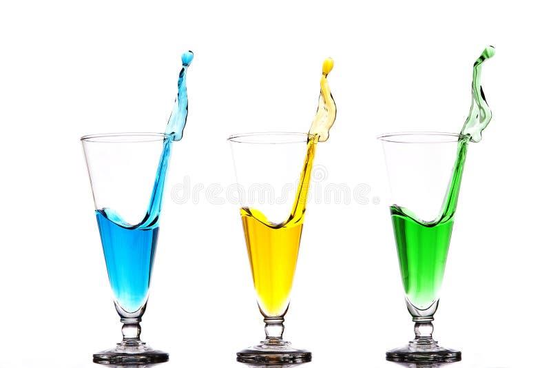 Tre exponeringsglas med färgrika färgstänk arkivbild