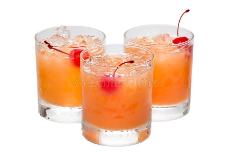 Tre exponeringsglas med orange coctails i det närbild royaltyfri fotografi