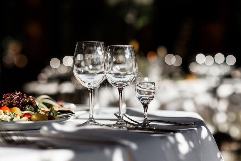 Tre exponeringsglas på en matställetabell royaltyfria bilder