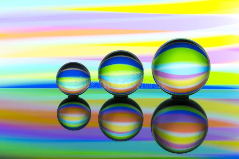Tre exponeringsglaskristallkulor i rad med en regnbåge av färgrik ljus målning bak dem arkivbilder