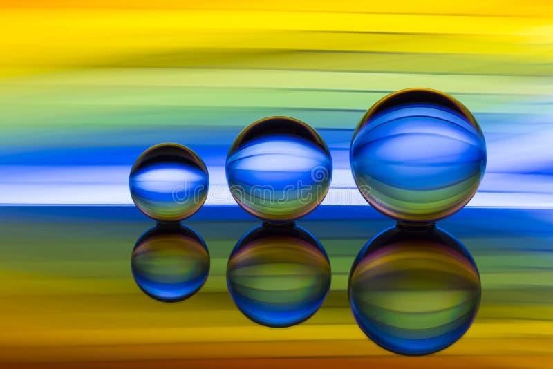 Tre exponeringsglaskristallkulor i rad med en regnbåge av färgrik ljus målning bak dem royaltyfri fotografi