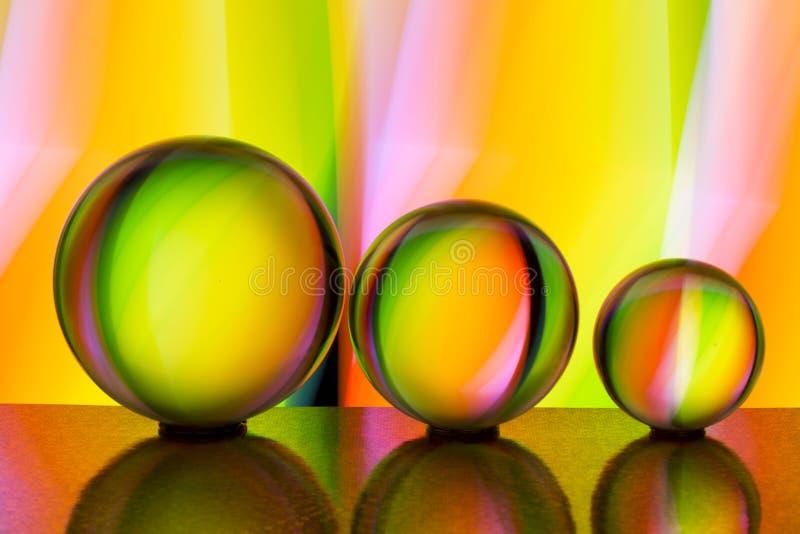 Tre exponeringsglaskristallkulor i rad med en regnbåge av färgrik ljus målning bak dem royaltyfria foton