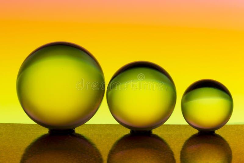 Tre exponeringsglaskristallkulor i rad med en regnbåge av färgrik ljus målning bak dem fotografering för bildbyråer