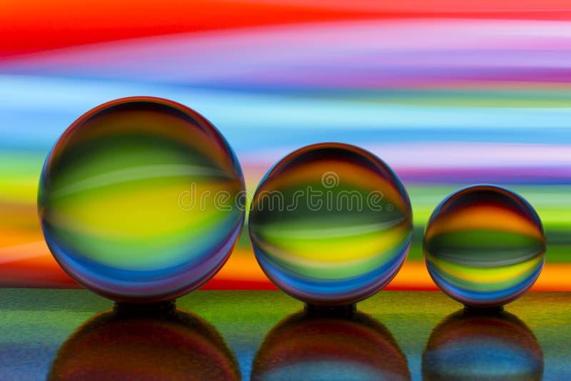 Tre exponeringsglaskristallkulor i rad med en regnbåge av färgrik ljus målning bak dem royaltyfri foto