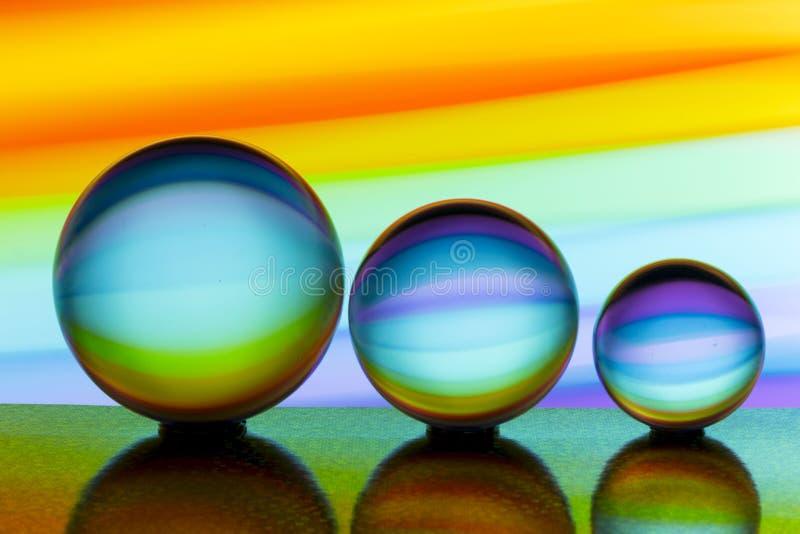 Tre exponeringsglaskristallkulor i rad med en regnbåge av färgrik ljus målning bak dem arkivfoto