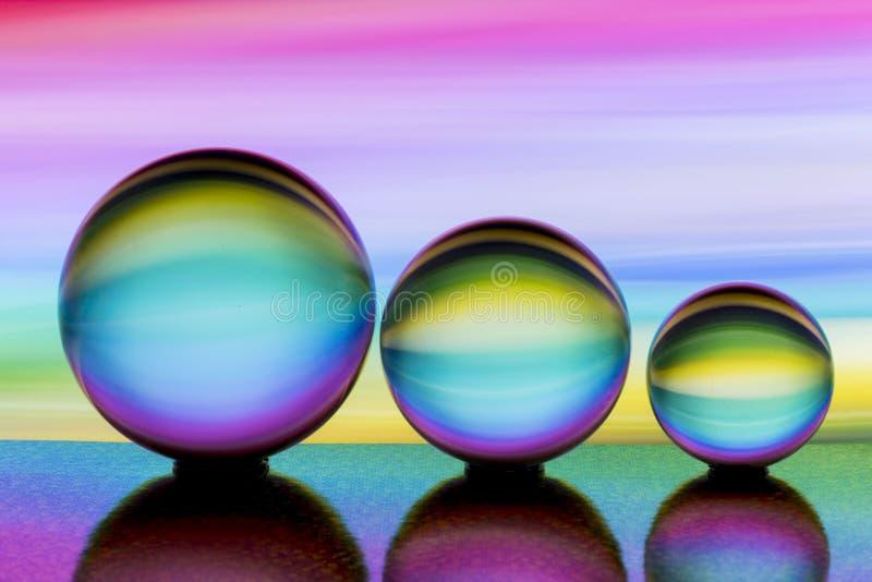 Tre exponeringsglaskristallkulor i rad med en regnbåge av färgrik ljus målning bak dem arkivbild