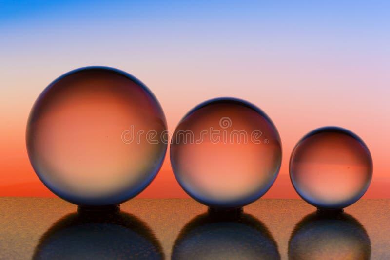 Tre exponeringsglaskristallkulor i rad med en regnbåge av färgrik ljus målning bak dem royaltyfri bild
