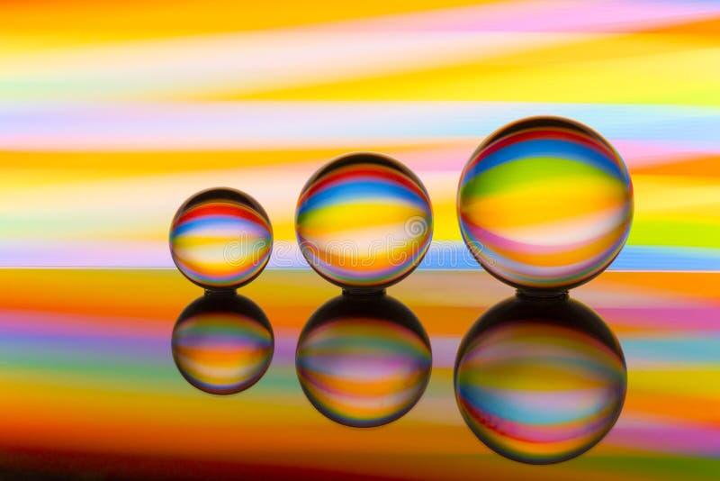 Tre exponeringsglaskristallkulor i rad med en regnbåge av färgrik ljus målning bak dem arkivfoton