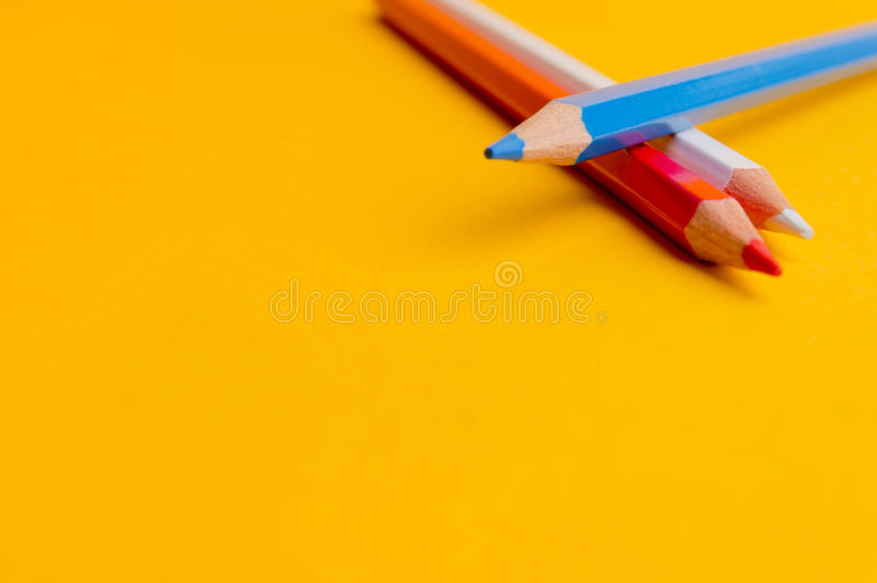 Tre färgade blyertspennor på gul bakgrund royaltyfria foton