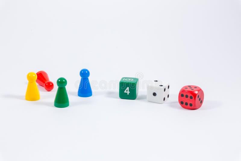 Tre färgade tärning och fyra spela stenar som isoleras på vitbac royaltyfri foto