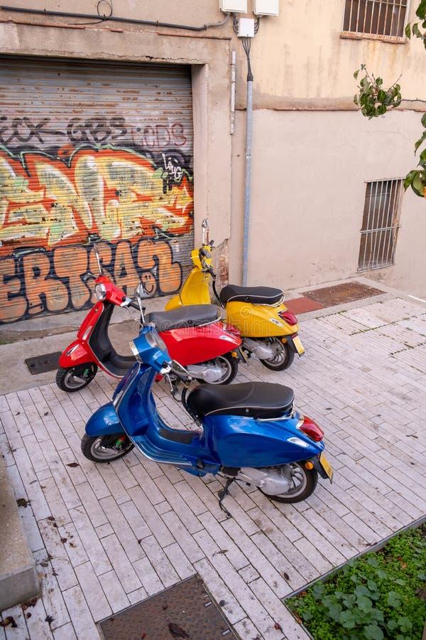 Tre f?rgglade retro sparkcyklar som st?r bredvid de p? gatan i Barcelona, Spanien arkivfoto