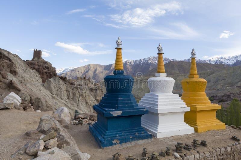 Tre färgglade tibetana buddistiska religiösa stupas nära en Buddhis royaltyfri bild