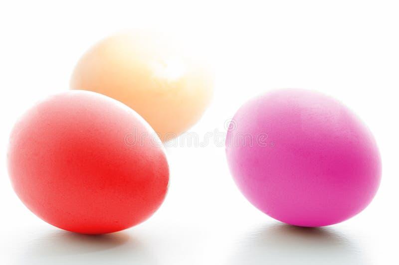 Tre färgrika ägg som isoleras på vit tom bakgrund royaltyfri bild
