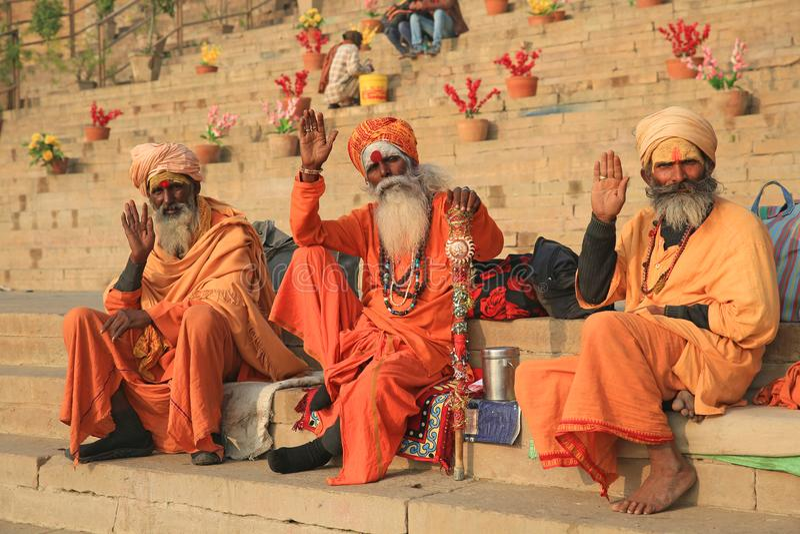 Tre färgrika asketer ger en ottavåg i Varanasi, Indien arkivfoto